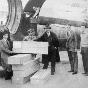 Charles E. Pennock and several employees assist in loading flower boxes on a DC-3.